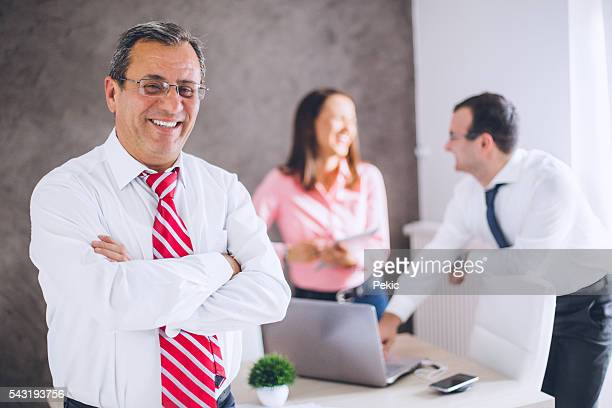 Smiling mature businessman with crossed arms in the office