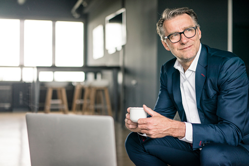 Smiling mature businessman with cup of coffee thinking - gettyimageskorea