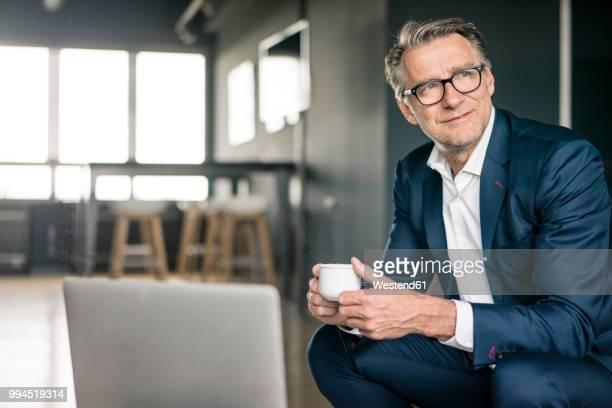 smiling mature businessman with cup of coffee thinking - mann kaffee stock-fotos und bilder