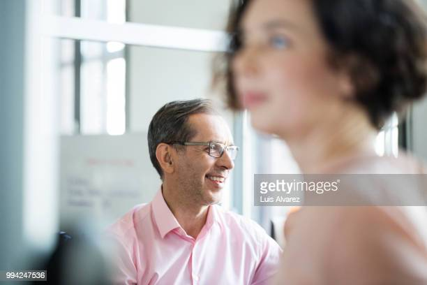 smiling mature businessman with female colleague - foco diferencial imagens e fotografias de stock