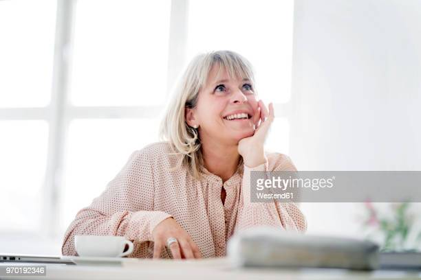 Smiling mature businesswoman at desk looking up
