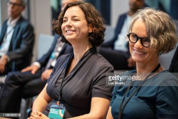 smiling mature businesswoman attending seminar - attending fotografías e imágenes de stock