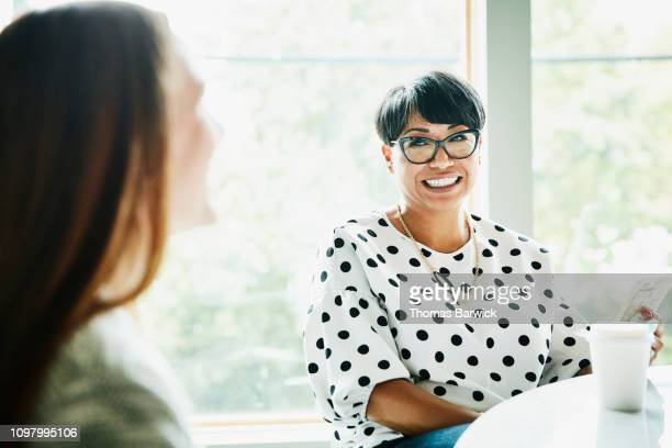 smiling mature businesswoman in discussion with colleague in office conference room - business finance and industry stock pictures, royalty-free photos & images