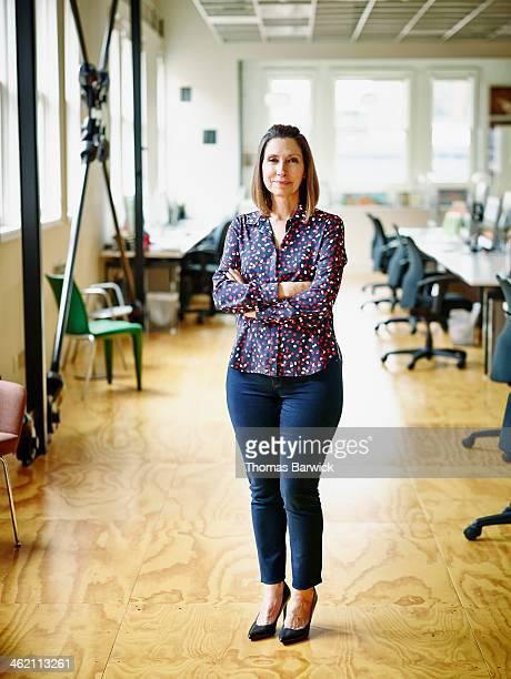 smiling mature businesswoman in high tech office - femme 50 ans brune photos et images de collection