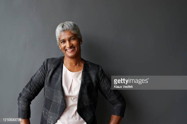 smiling mature businesswoman in office board room - businesswoman stock pictures, royalty-free photos & images
