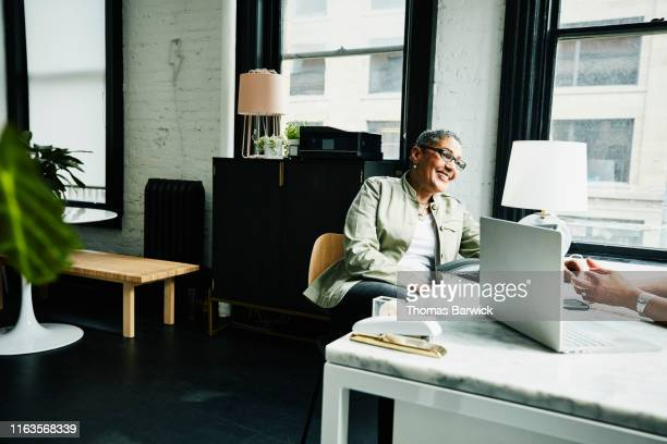smiling mature businesswoman in planning meeting in small office - small office stock pictures, royalty-free photos & images