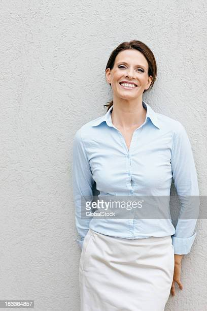Smiling, mature businesswoman leaning against a wall