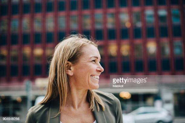 Smiling mature businesswoman looking away against building in city