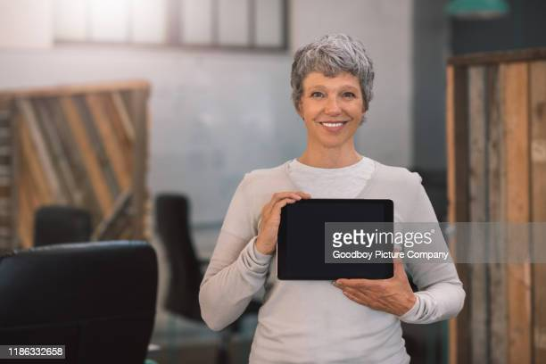 smiling mature businesswoman presenting a tablet with a blank screen - holding aloft stock pictures, royalty-free photos & images