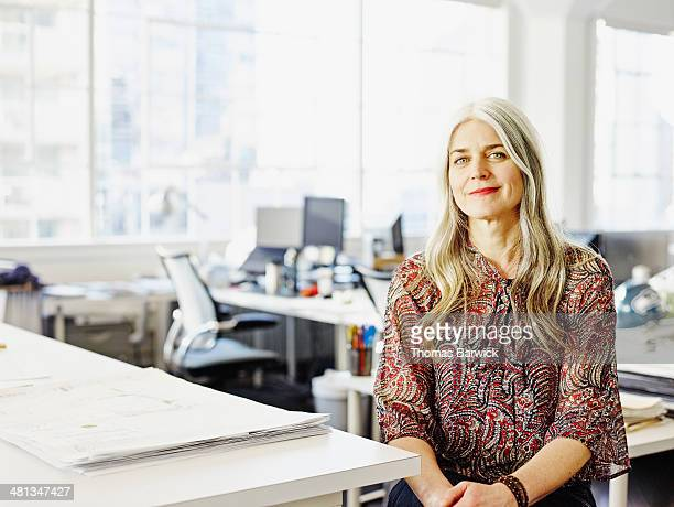 Smiling mature businesswoman sitting in office