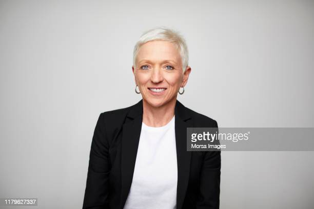smiling mature businesswoman wearing black blazer - 50 54 years stock pictures, royalty-free photos & images