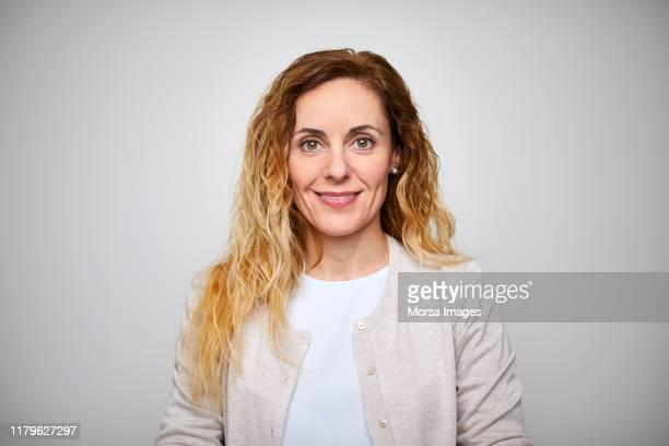smiling mature businesswoman with long blond hair - occhi nocciola foto e immagini stock