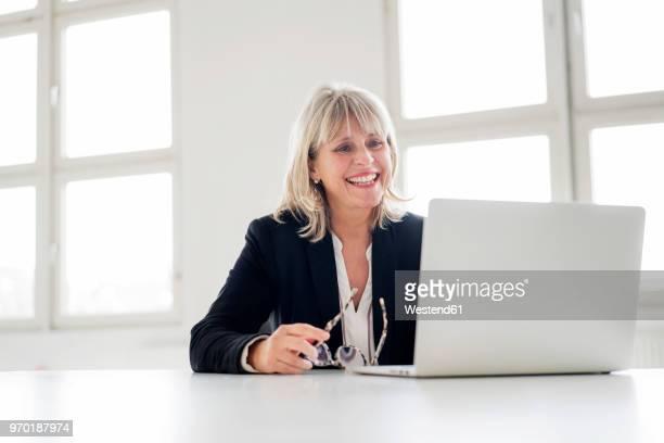 smiling mature businesswoman working on laptop at desk in the office - solo una donna matura foto e immagini stock