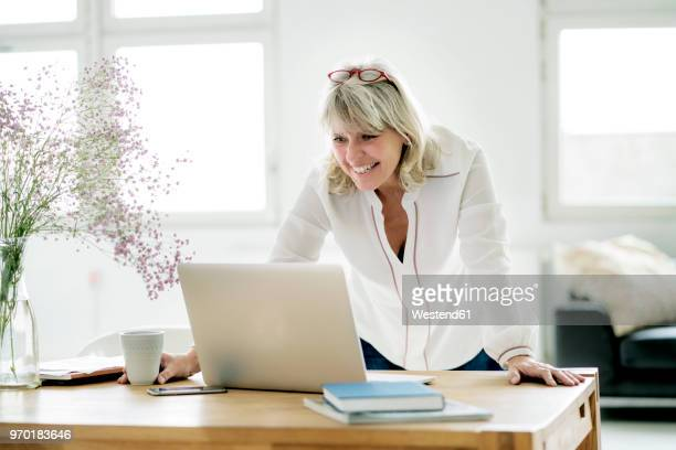 smiling mature businesswoman working on laptop at desk - good news stock pictures, royalty-free photos & images