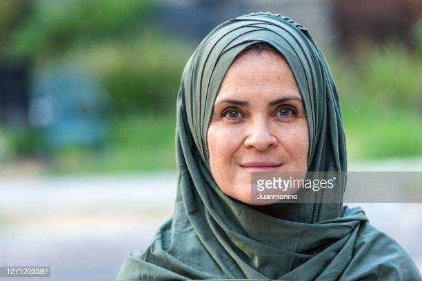 smiling mature caucasian muslim woman looking at the camera - holy city park stock pictures, royalty-free photos & images