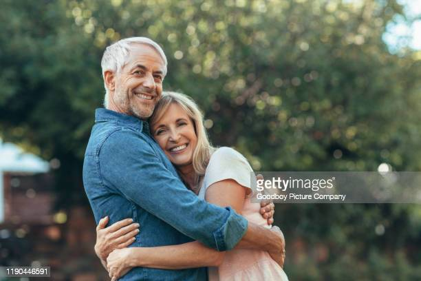smiling mature couple affectionatley hugging each other outside - mature couple stock pictures, royalty-free photos & images