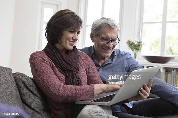 Smiling mature couple at home on the sofa using laptop