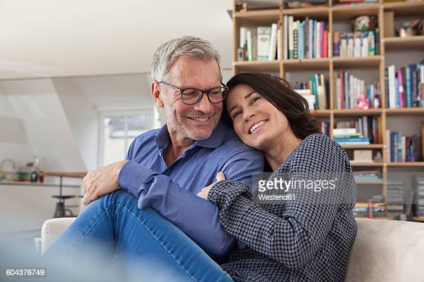 Smiling mature couple cuddling at home