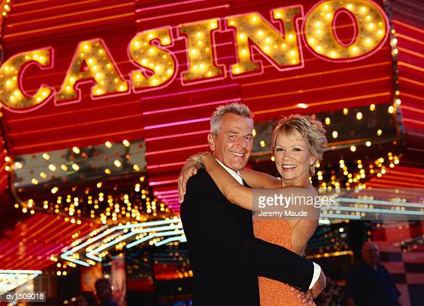 Smiling, Mature Couple Cuddling in Front of a Casino