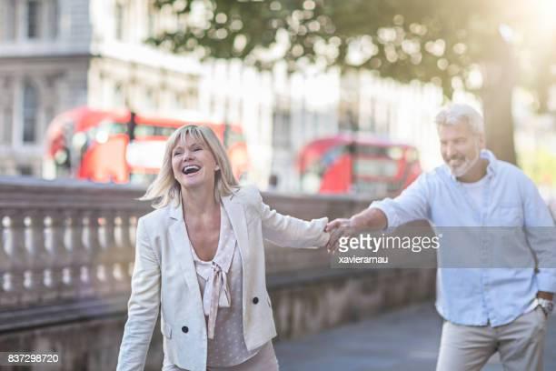 lächelnd reife paare, die spaß in london - südostengland stock-fotos und bilder