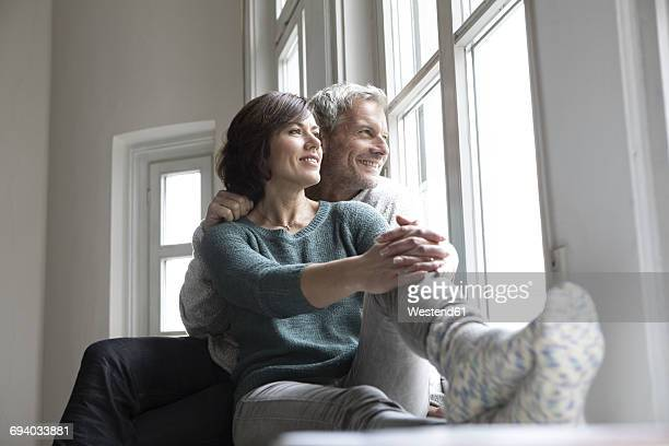 Smiling mature couple looking out of window