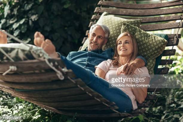 lächelndes reifes paar liegt zusammen in einer hängematte draußen - ehefrau stock-fotos und bilder
