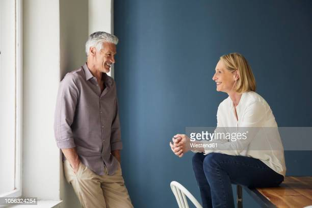 smiling mature couple relaxing at home - heterosexual couple stock pictures, royalty-free photos & images