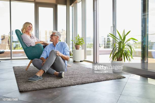 smiling mature couple relaxing at home - ricchezza foto e immagini stock