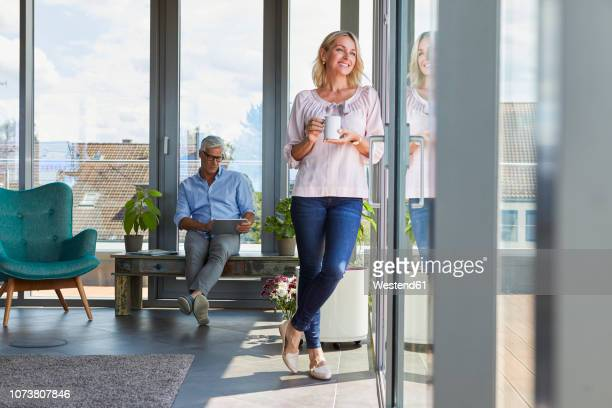 smiling mature couple relaxing at home with woman looking out of window and man using tablet - woman sitting on man's lap stock pictures, royalty-free photos & images