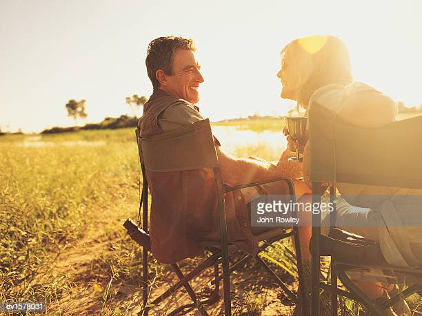 Smiling, Mature Couple Sitting in Grassland on Safari in the Sunlight