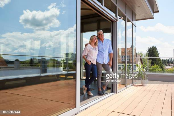 smiling mature couple standing at roof terrace at home - eigenheim stock-fotos und bilder