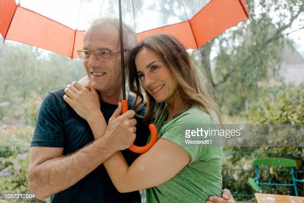 smiling mature couple standing in rain under umbrella - women in wet t shirts stock pictures, royalty-free photos & images