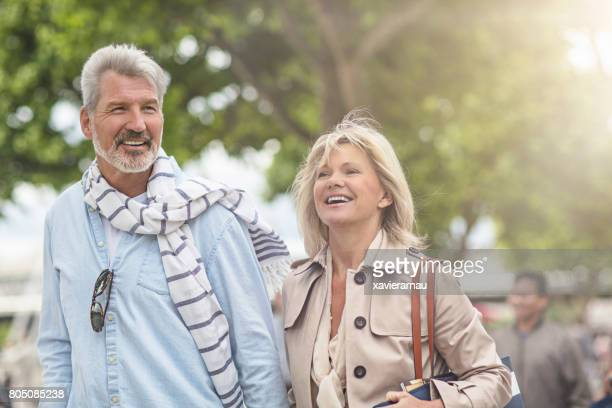 Smiling mature couple walking in city