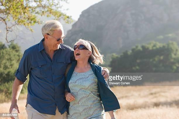 Sonriente pareja madura pasos en las montañas
