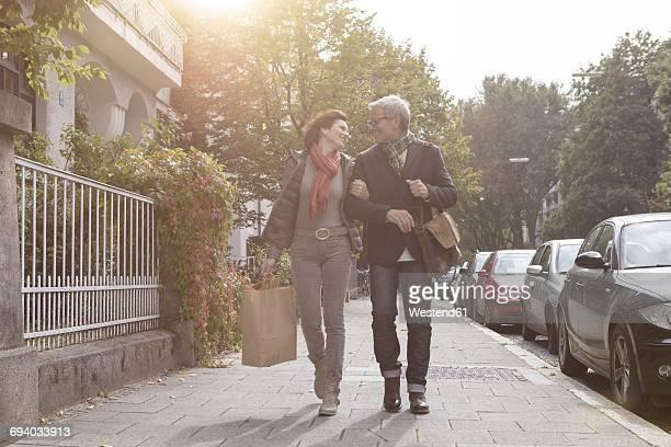 Smiling mature couple walking on pavement