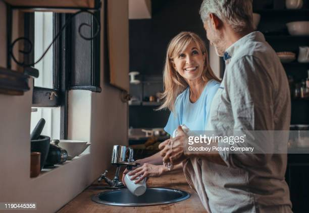 smiling mature couple washing dishes in their kitchen - couples showering stock pictures, royalty-free photos & images