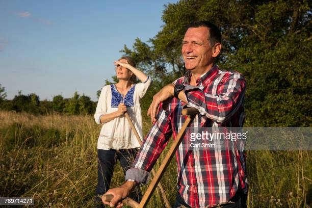 smiling mature couple with equipment standing at farm on sunny day - squinting stock photos and pictures