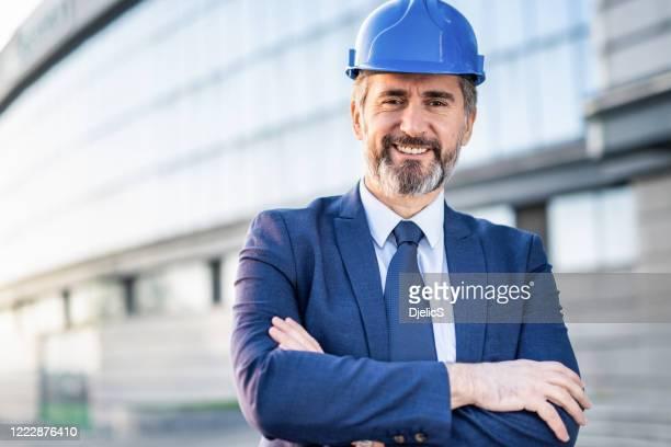 ingeniero maduro sonriente con los brazos cruzados mirando a la cámara. - ingeniero civil fotografías e imágenes de stock
