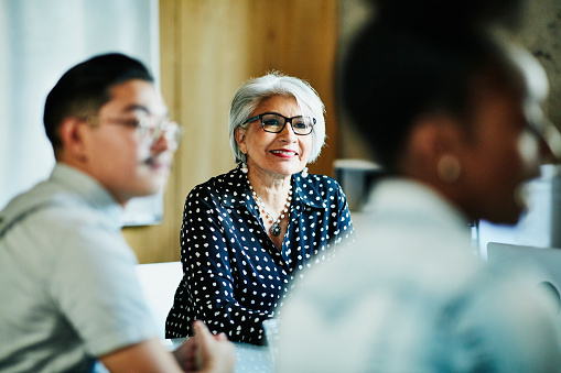 Smiling mature female business owner listening during presentation during meeting in office conference room - gettyimageskorea