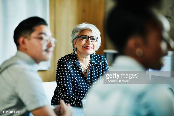 smiling mature female business owner listening during presentation during meeting in office conference room - small business or entrepreneur stock photos and pictures