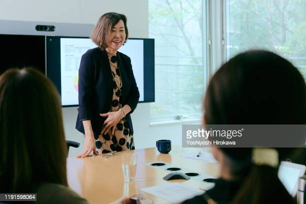 smiling mature female business owner talking during presentation during meeting in office conference room - oost azië stockfoto's en -beelden