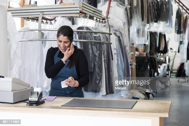 smiling mature female cleaner talking on smart phone while standing at laundromat - dry cleaner stock pictures, royalty-free photos & images