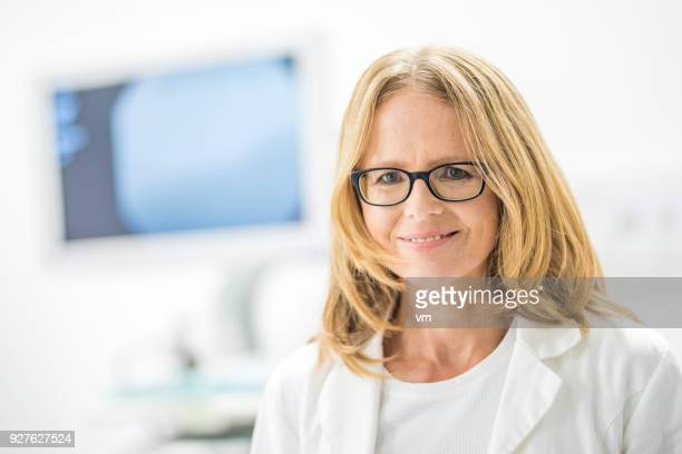 Smiling mature female doctor with blond hair and glasses