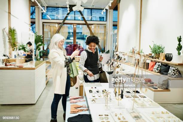 smiling mature female friends admiring jewelry while shopping together in boutique - shopping stock pictures, royalty-free photos & images
