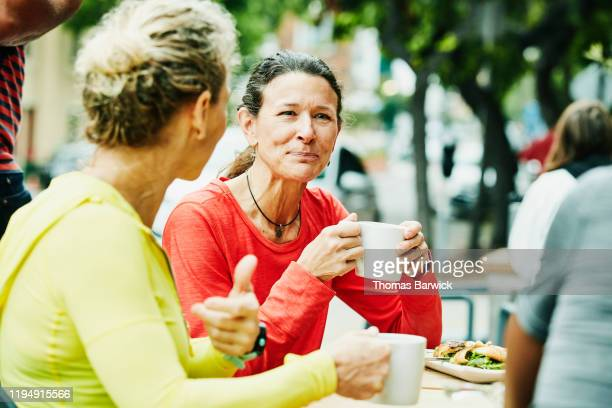 smiling mature female friends enjoying breakfast at outdoor cafe after morning run - disruptagingcollection fotografías e imágenes de stock