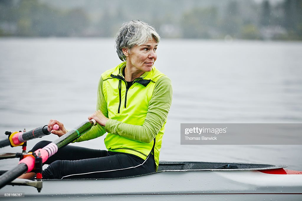 Smiling mature female rower looking over shoulder : Stock Photo
