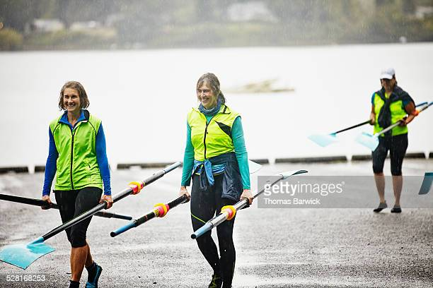 Smiling mature female rowers carrying oars in rain