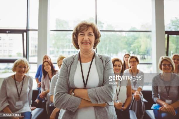 smiling mature female speaker at seminar - izusek stock pictures, royalty-free photos & images