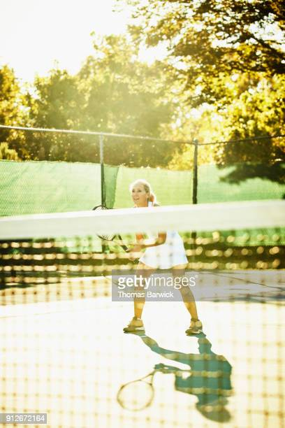 Smiling mature female tennis player playing at net during early morning tennis match