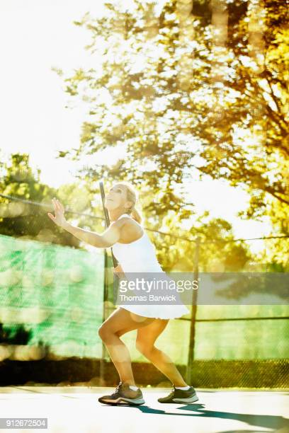 Smiling mature female tennis player preparing to hit overhead shot during early morning match